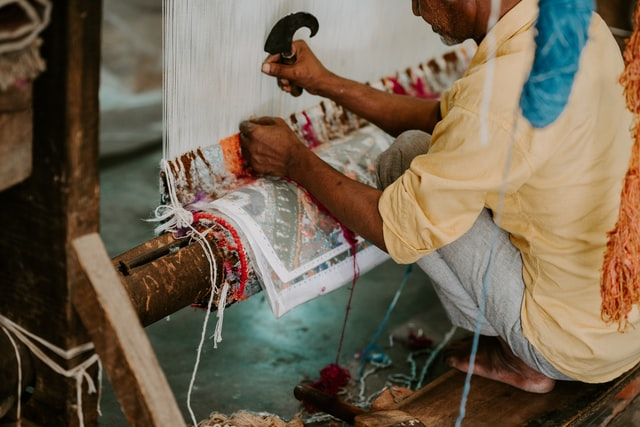 Man weaving a rug by hand