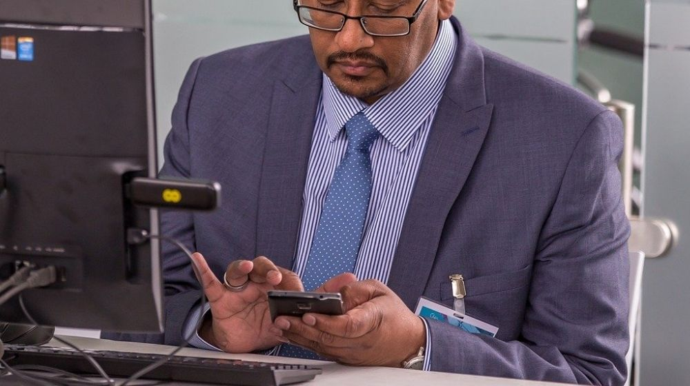 IT consultant sitting at his desk with a smartphone