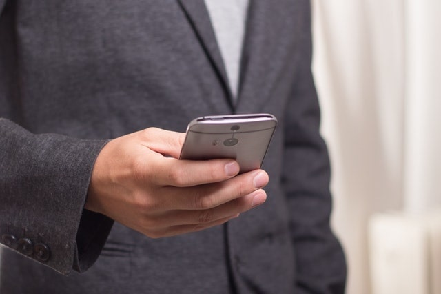 Man in a gray suit coat using a smartphone
