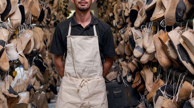 Man Wearing Apron Standing Between Racks of Shoe Molds
