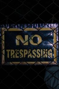 No Trespassing Sign on Black Wire Fence