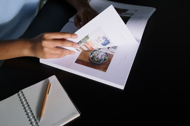 Person leafing through a graphic design catalog