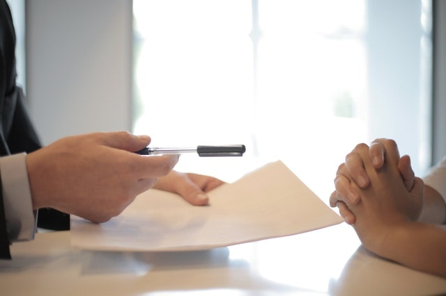 Person offering a contract and pen to another