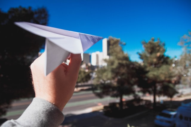 closeup of a hand holding a paper airplane