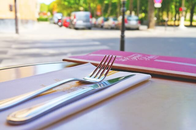 Close-up of dining utensils next to menu on table with street level views in background