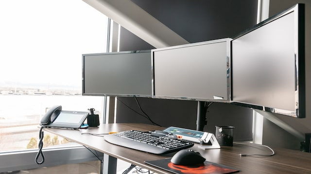 Desktop computer with three screens on a desk