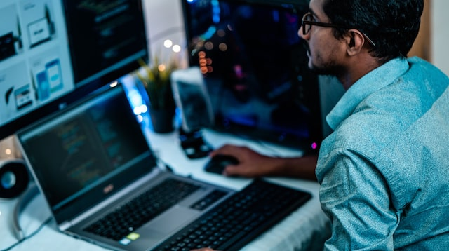 Developer at a desk with a laptop and second monitor