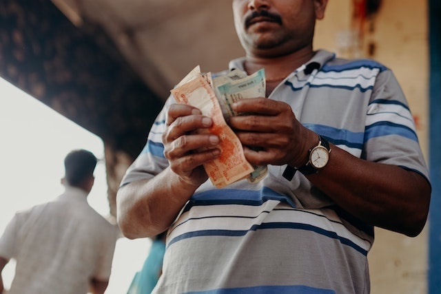 Man counting money outside a shop