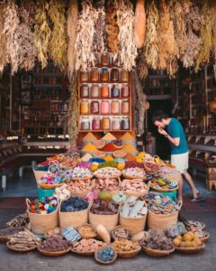Man standing in marketplace looking at spices for sale