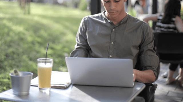 Man using a laptop at an outdoor cafe
