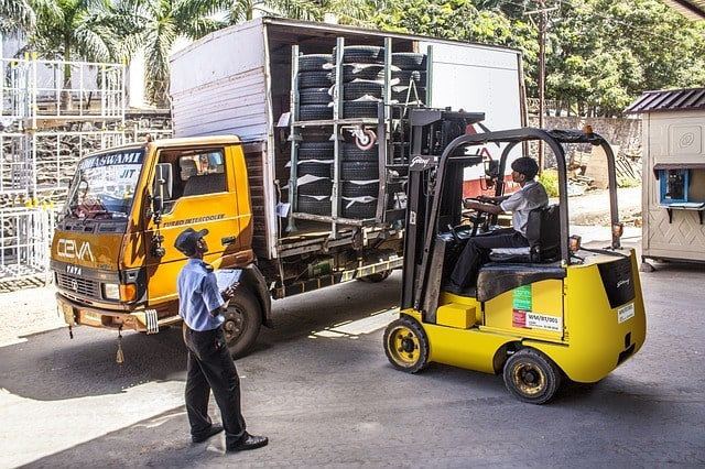Men unloading tires from a truck with a forklift