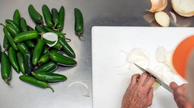 Person chopping vegetables in a commercial kitchen