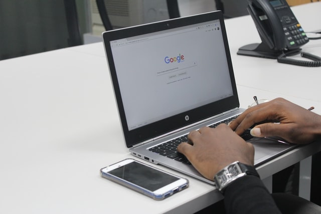 Person doing a Google search on a laptop