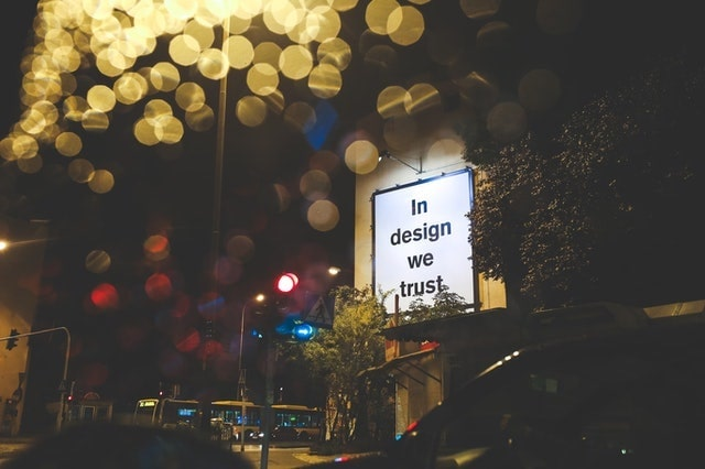 """Photo showing a signboard reading """"In design we trust"""""""