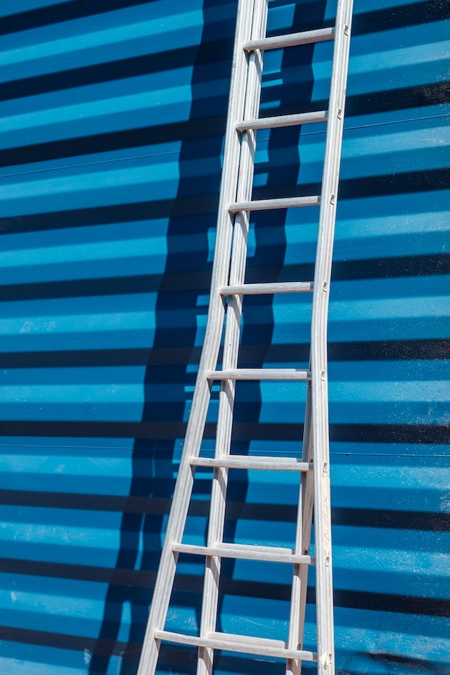 Recruiting Employees Ladder Leaning Against Striped Wall